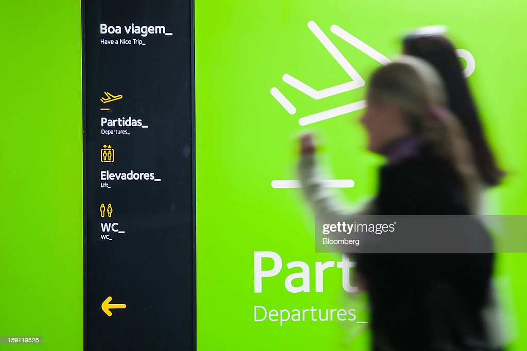 Passengers walk past a departures sign at Lisbon International (Portela) airport, operated by ANA-Aeroportos de Portugal SA, in Lisbon, Portugal, on Tuesday, Jan. 8, 2013. Portugal's government agreed to sell state-owned airport operator ANA-Aeroportos de Portugal SA to Vinci SA for 3.08 billion euros ($4.07 billion), raising money for the debt-strapped country. Photographer: Mario Proenca/Bloomberg via Getty Images