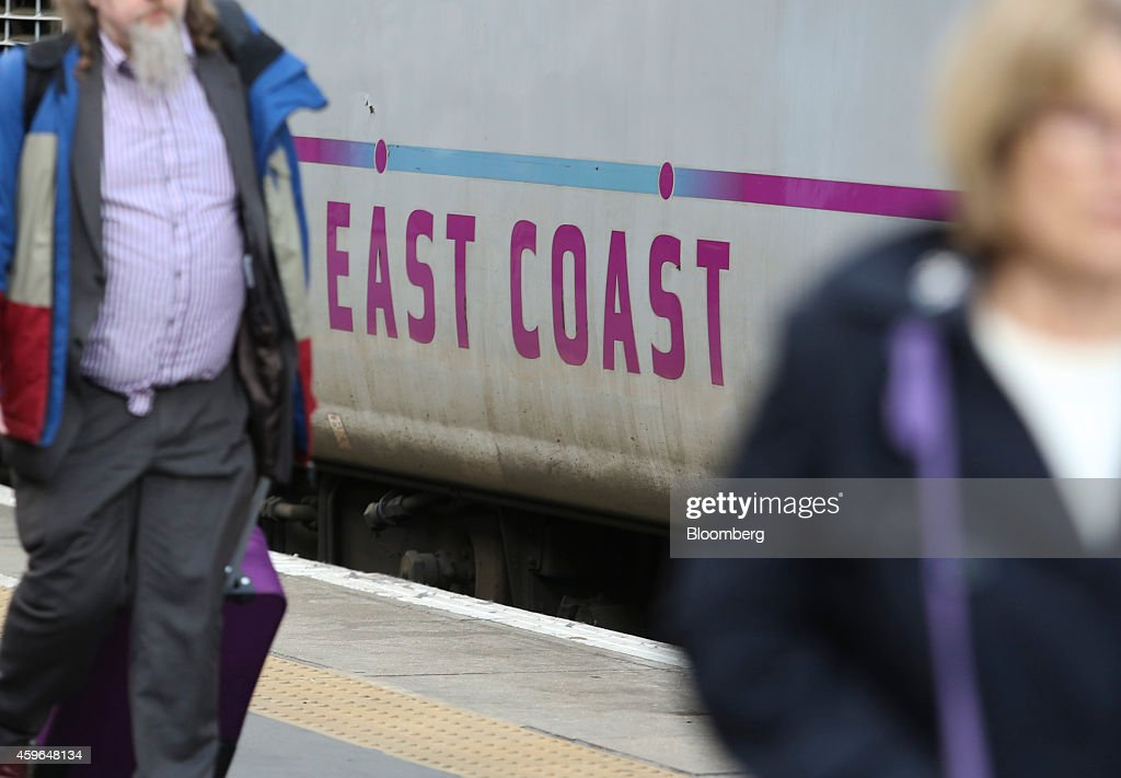 Passengers walk past an East Coast Main Line train, operated by government-appointed Directly Operated Railways Ltd., at Kings Cross railway station in London, U.K., on Thursday, Nov. 27, 2014. Virgin Trains and partner Stagecoach Group Plc were chosen to run the London-Edinburgh rail route, fending off rival bids from FirstGroup Plc and Eurostar International Ltd. and delivering a boost for Richard Branson a month after the fatal crash involving his space venture. Photographer: Chris Ratcliffe/Bloomberg via Getty Images