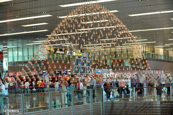 Passengers walk past Kinetic Rain reportedly the world's largest kinetic art sculpture hanging in the departure checkin hall in Singapore's Changi...