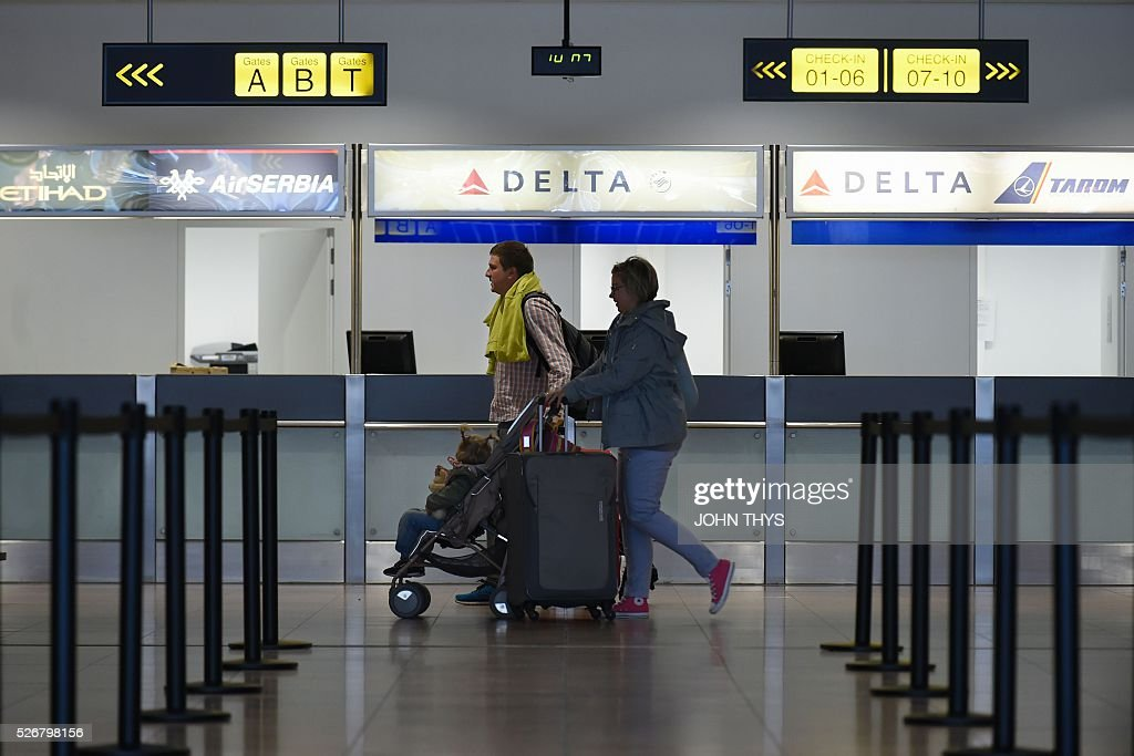 Passengers walk past the desk of US airline Delta Air Lines as they arrive at a temporary check-in area during the partial reopening of the departure hall of Brussels Airport in Zaventem on May 1, 2016, after it was badly damaged in twin suicide attacks on March 22, that killed 16 people. A total of 32 people were killed and more than 300 wounded in coordinated suicide bombings at the airport and a metro station in central Brussels on March 22 in Belgium's worst ever terror attacks. / AFP / JOHN