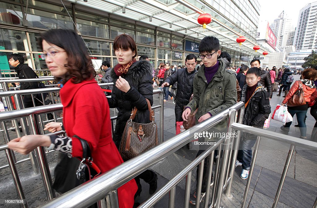 Passengers walk through a gate as they enter Shanghai Railway Station in Shanghai, China, on Sunday, Feb. 3, 2013. Forecasts of snow and rain across China threaten to disrupt the travel plans of millions of Chinese heading home for the Lunar New Year holidays that start Feb. 9, the national weather agency warned. Photographer: Tomohiro Ohsumi/Bloomberg via Getty Images