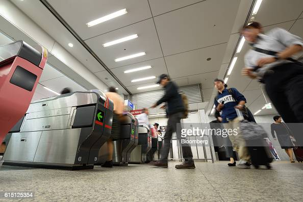 Passengers walk through automated ticket gates at Hakata Station in Fukuoka Fukuoka Prefecture Japan on Tuesday Oct 11 2016 Kyushu Railway Co the...