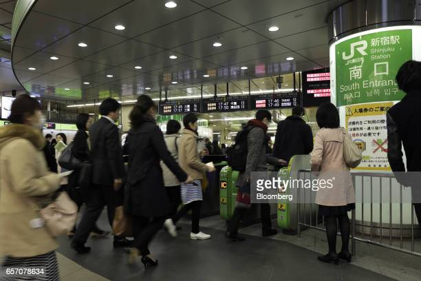 Passengers walk through automatic ticket gates at East Japan Railway Co's Shinjuku Station in Tokyo Japan on Thursday March 23 2017 JR East the...