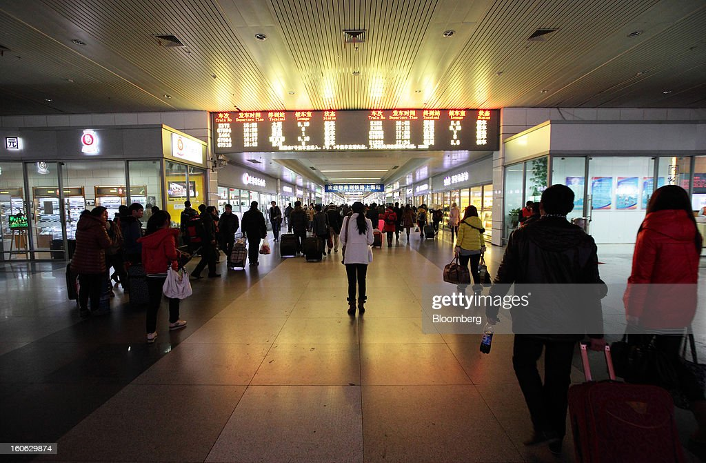 Passengers walk through Shanghai Railway Station in Shanghai, China, on Sunday, Feb. 3, 2013. Forecasts of snow and rain across China threaten to disrupt the travel plans of millions of Chinese heading home for the Lunar New Year holidays that start Feb. 9, the national weather agency warned. Photographer: Tomohiro Ohsumi/Bloomberg via Getty Images