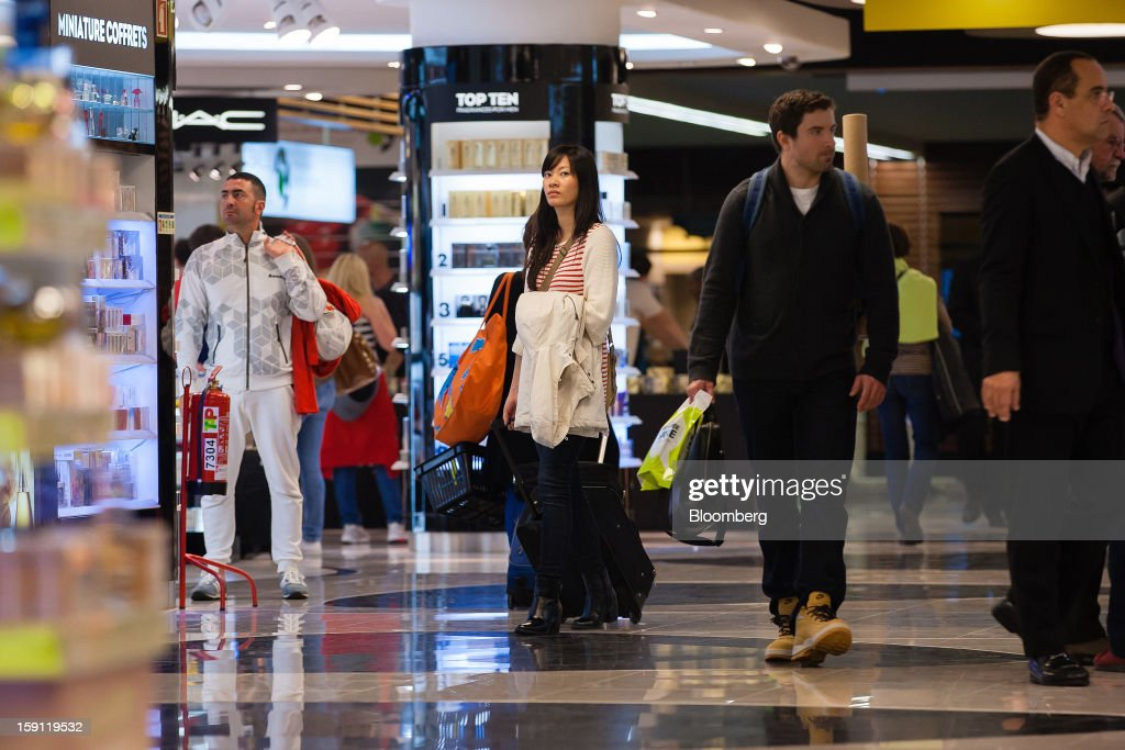 Passengers walk through the duty free shopping section of Lisbon International (Portela) airport, operated by ANA-Aeroportos de Portugal SA, in Lisbon, Portugal, on Tuesday, Jan. 8, 2013. Portugal's government agreed to sell state-owned airport operator ANA-Aeroportos de Portugal SA to Vinci SA for 3.08 billion euros ($4.07 billion), raising money for the debt-strapped country. Photographer: Mario Proenca/Bloomberg via Getty Images