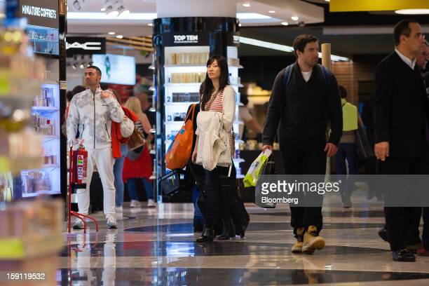 Passengers walk through the duty free shopping section of Lisbon International airport operated by ANAAeroportos de Portugal SA in Lisbon Portugal on...