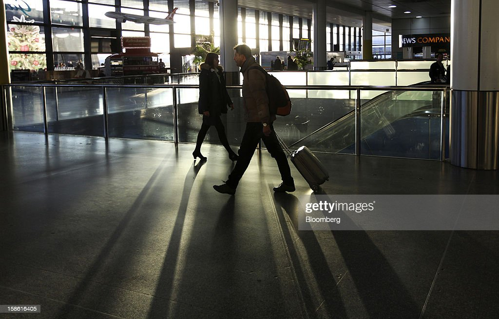 Passengers walk through the north terminal at Gatwick airport in Crawley, U.K., on Friday, Dec. 21, 2012. U.K. airports predicted today to be the busiest day during the Christmas period, as some Britons opt to spend the holidays abroad and overseas visitors fly out to be with friends and family. Photographer: Chris Ratcliffe/Bloomberg via Getty Images