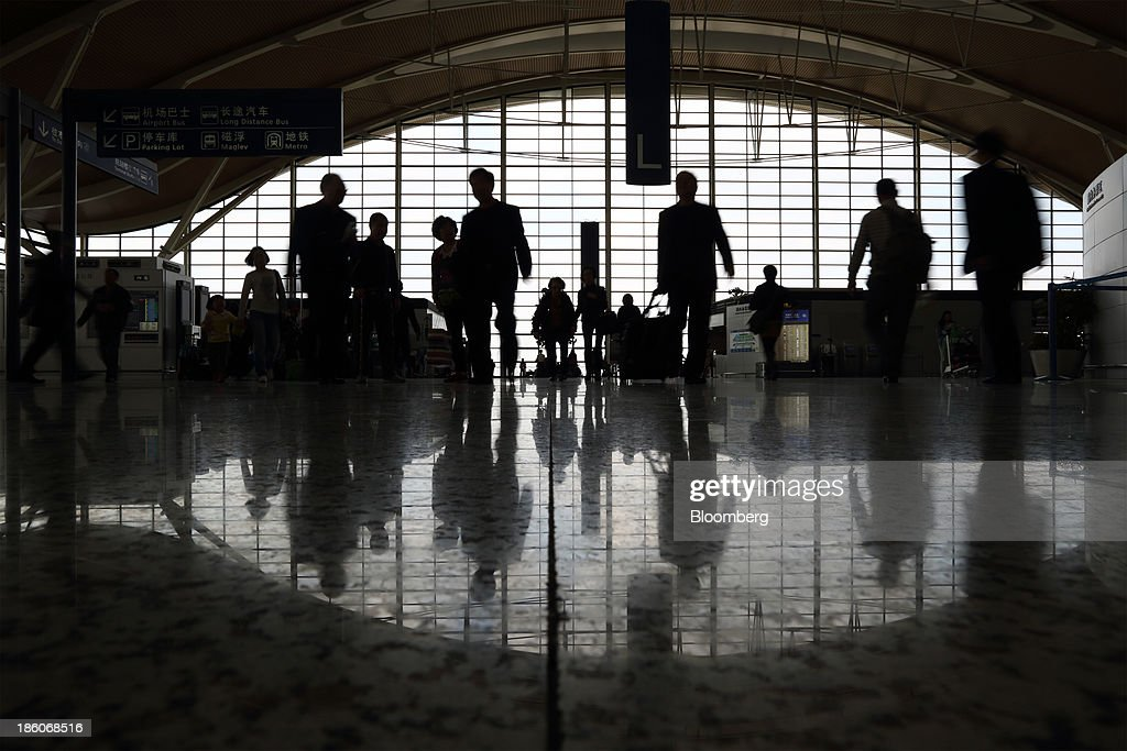Passengers walk through the terminal building of Shanghai Pudong International Airport in Shanghai, China, on Saturday, Oct. 26, 2013. Airline profits worldwide in 2013 will be 7.9 percent smaller than estimated at $11.7 billion amid sluggish travel demand and rising oil prices tied to the Syria crisis, the International Air Transport Association said last month. Photographer: Tomohiro Ohsumi/Bloomberg via Getty Images