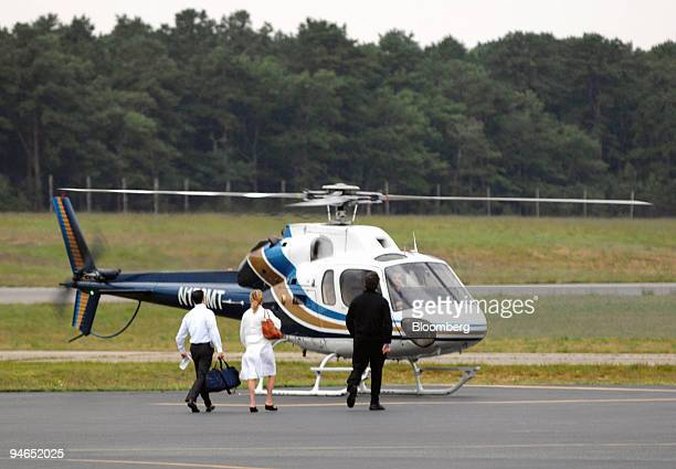 Passengers walk to a helicopter before departing the East Hampton Airport in East Hampton New York on Aug 13 2007