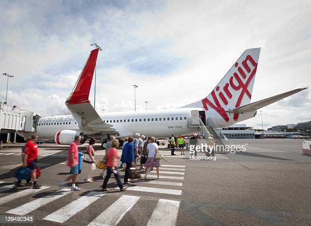 Passengers walk to board a Virgin Australia Holdings Ltd Boeing 737800 aircraft at the domestic terminal of Sydney airport in Sydney Australia on...