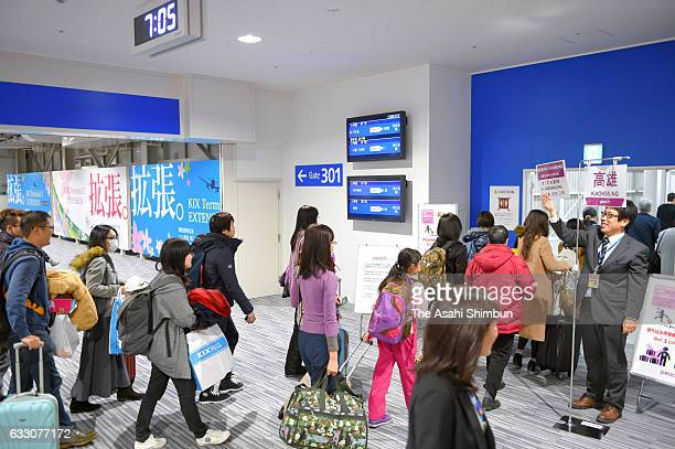 Passengers walk to board their airplane at the new terminal for low cost carriers at Kansai International Airport on January 28 2017 in Izumisano...
