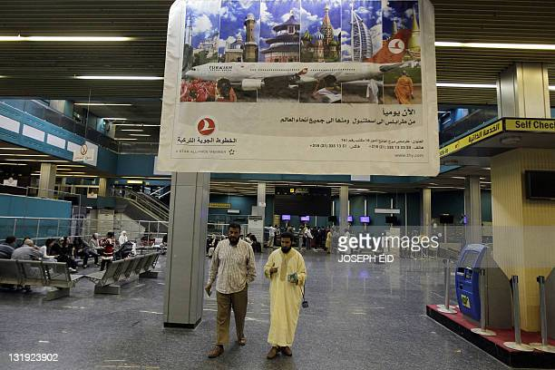 Passengers walk under a billboard advertiising trips to Istanbul on Turkish airlines on November 8 2011 at the departure terminal of Tripoli's...