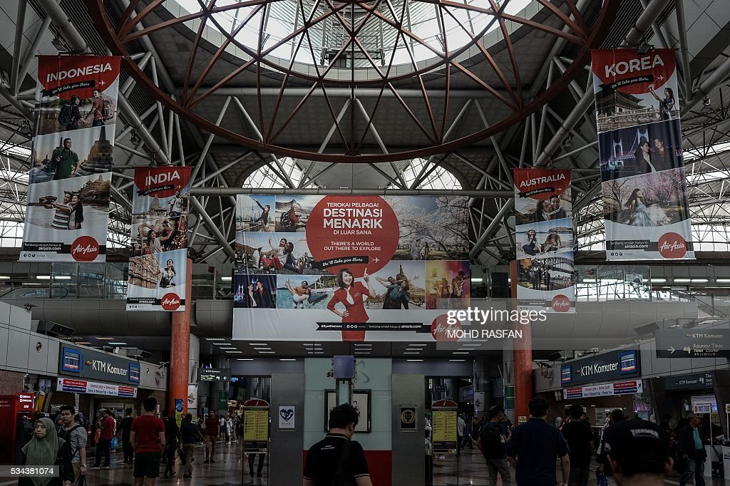Passengers walk under AirAsia advertisements at Kuala Lumpur Sentral railway station in Kuala Lumpur on May 26, 2016. Malaysia's Budget carrier AirAsia was expected to announce its first quarter results on the back of lower oil prices on May 26. / AFP / MOHD