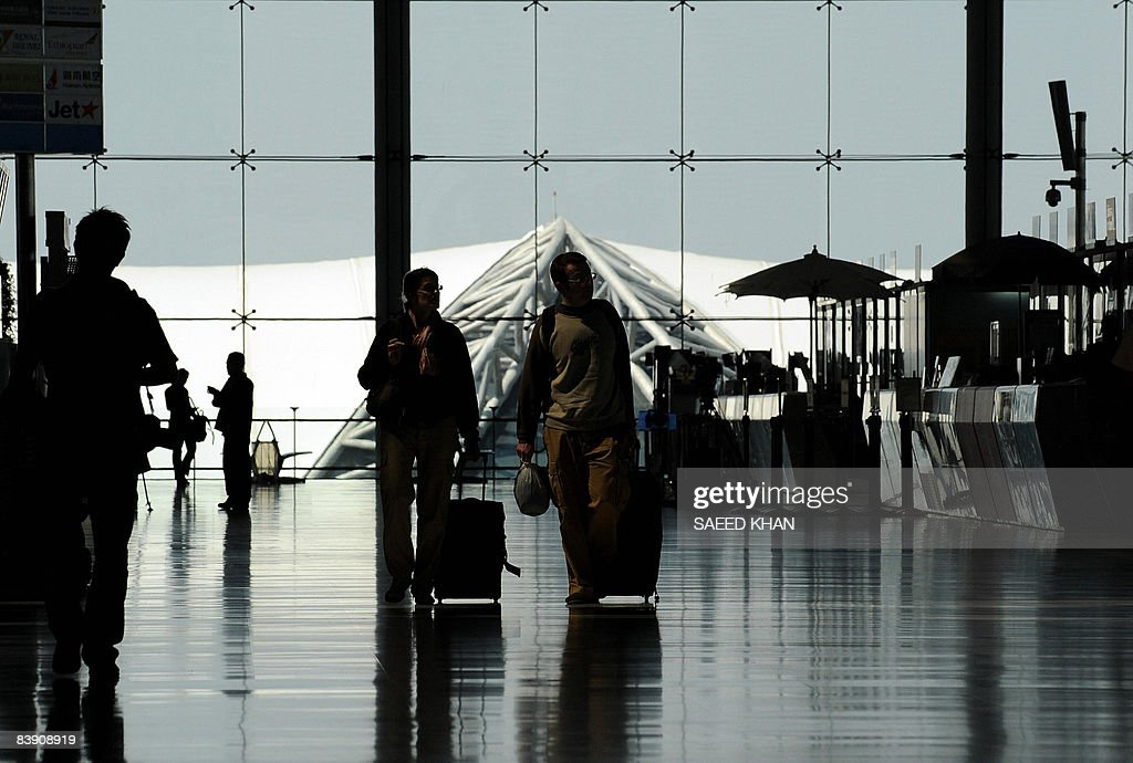 Passengers walk with their luggage at the departure lounge of the Suvarnabhumi Airport in Bangkok on December 4 2008 Thai Airways is planning to sue...