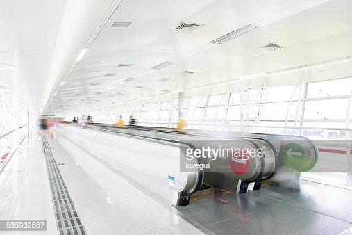 passengers walking in the corridor with escalator : Stock Photo