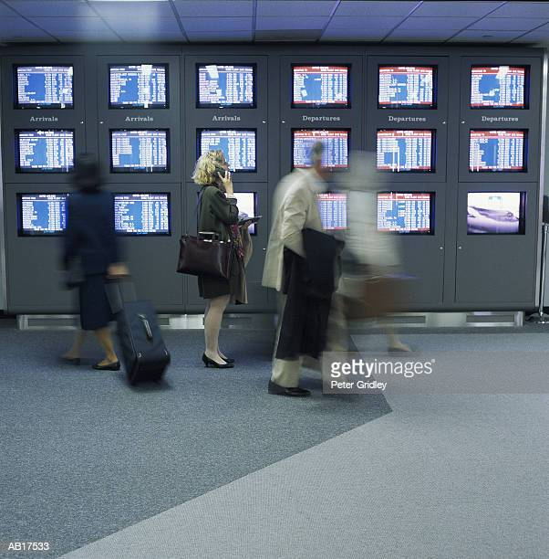Passengers walking past arrival and departure board in airport terminal