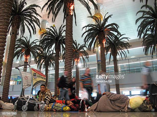 Passengers walking to their departure lounge pass travellers sleeping on the floor of a terminal at Dubai International Airport Al Garhoud United...