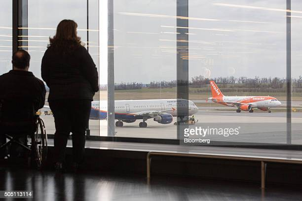 Passengers watch as an Easyjet Plc passenger aircraft taxis on the tarmac at Vienna International Airport operated by Flughafen Wien AG in Vienna...