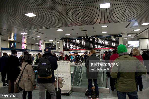 Passengers watch departure board for New Jersey Transit and Amtrak trains at Pennsylvania Station New York City USA