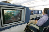 Passengers watch inflight entertainment on Cathay Pacific plane 12 April 2005 AFP PHOTO/MIKE CLARKE