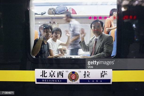 Passengers wave as the first train from Beijing West Railway Station leaves for Lhasa Tibet on July 2 2006 in Beijing China