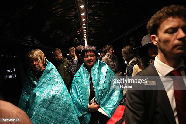 Passengers wear emergency blankets to keep warm as they queue outside the terminal after it was evacuated at London City Airport following a chemical...