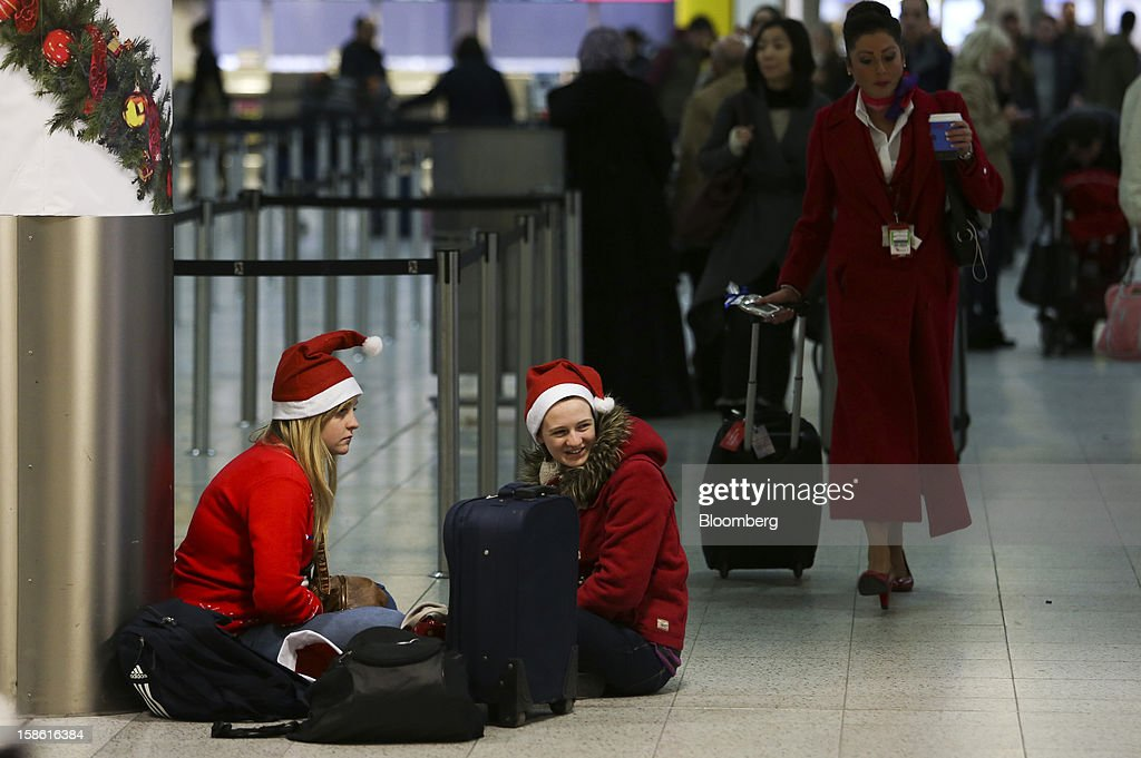 Passengers wear festive Santa Claus hats as they sit with their luggage in the check-in area of the south terminal at Gatwick airport in Crawley, U.K., on Friday, Dec. 21, 2012. U.K. airports predicted today to be the busiest day during the Christmas period, as some Britons opt to spend the holidays abroad and overseas visitors fly out to be with friends and family. Photographer: Chris Ratcliffe/Bloomberg via Getty Images