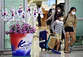 Passengers wearing face masks arrive at Gimpo international airport in Seoul on June 17 2015 South Korea on June 17 announced its 20th death from the...