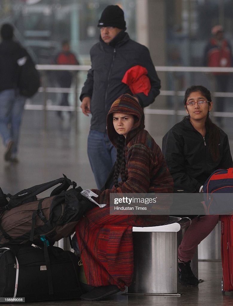 Passengers wearing warm clothes waiting at IGI Airport, as temperature dips below 6 degree Celsius on January 2, 2013 in New Delhi, India. There was no respite from cold and dense fog in North India as mercury dipped two degrees below normal to stay at 4.8 degree Celsius.