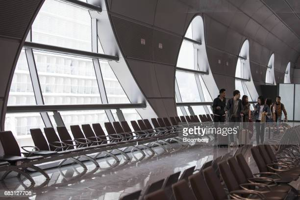 Passengers wheel their luggage through the departure concourse to board the Ovation of the Seas Quantumclass cruise ship operated by Royal Caribbean...