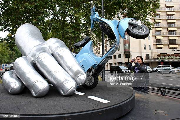A passer by admires Lorenzo Quinn's 'La Dolce Vita' sculpture as it is installed on Park Lane in Mayfair on September 30 2012 in London England The...