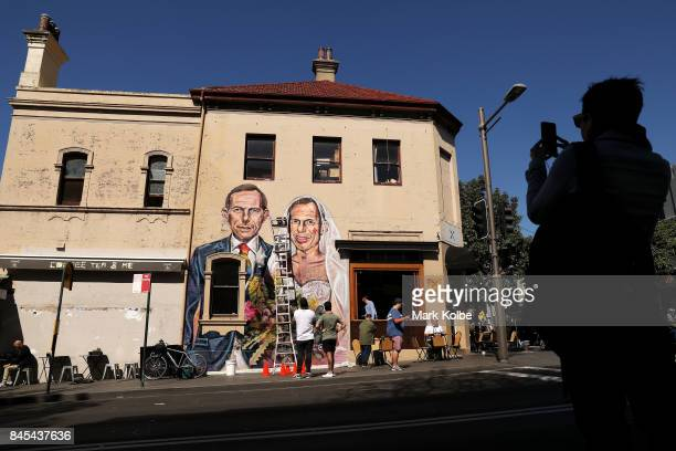 A passer by stops to photograph a mural by artist Scott Marsh depicting former Prime Minister Tony Abbott is seen in Redfern on September 11 2017 in...