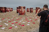 A passerbby takes pictures of some 420 panties and portraits of bloodstained womem set up by NGO Rio de Paz to protest against violence against women...