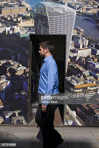 A passerby and an ad for London's skyline featuring the new WalkieTalkie building as Londoners experience the unexpected intensity of localised solar...