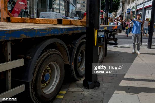 A passerby directs an articulated lorry as it squeezes past a pedestrian crossing post making a tight turn across the pavement on 1st August 2017 in...