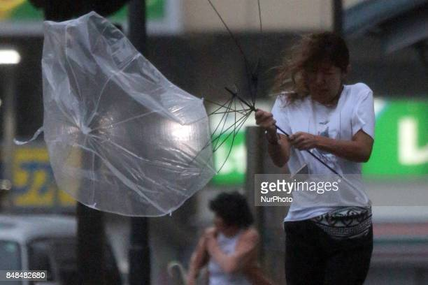 A passerby holding an umbrella struggles against the wind and Heavy rain and strong winds moved across the season's 18th typhoon in Oita Prefecture...