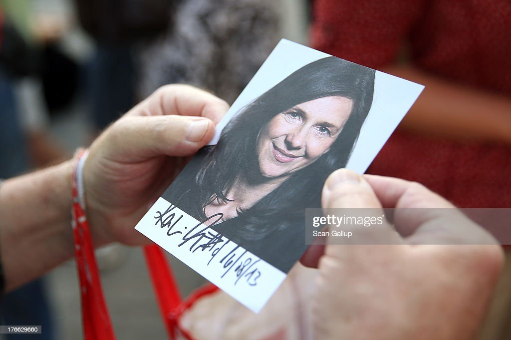 A passer-by holds an election campaign card showing and signed by German Greens Party (Buendnis 90/Die Gruenen) co-lead candidate Katrin Goering-Eckardt during an election campaign stop on August 16, 2013 in Leipzig, Germany. Germany is scheduled to hold federal elections on September 22 and the Greens could well play a decisive role in the formation of a government coalition.