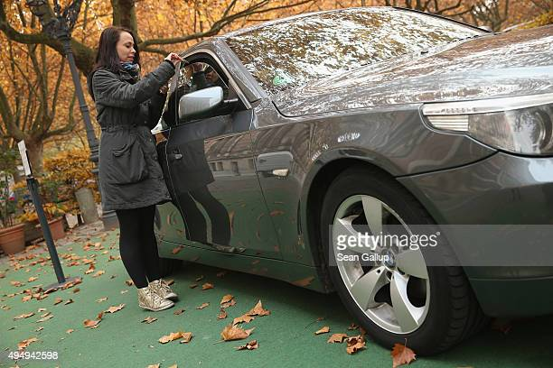 Passerby Lena Lauschuss drops Lego pieces she brought into a BMW car that is being used as a collection point for Lego donations for Chinese artist...