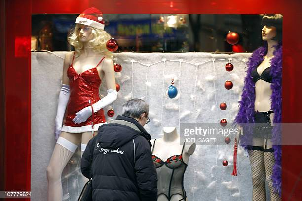 A passerby looks at a Christmas sexshop window in Pigalle red quarter in Paris on December 22 2010 AFP PHOTO JOEL SAGET