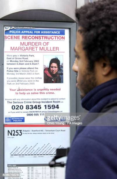 A passerby looks at a poster appealing for information relating to the murder of Margaret Muller posted at a bus stop in Hackney east London The...