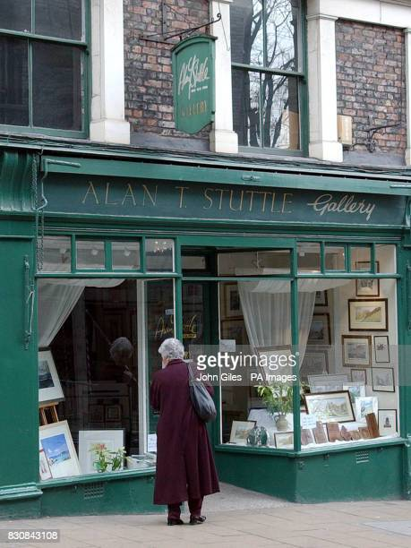 A passerby looks into a window of the art gallery in York owned by local artist Alan Stuttle Mr Stuttle's 19yearold daughter Caroline Ann Stuttle was...