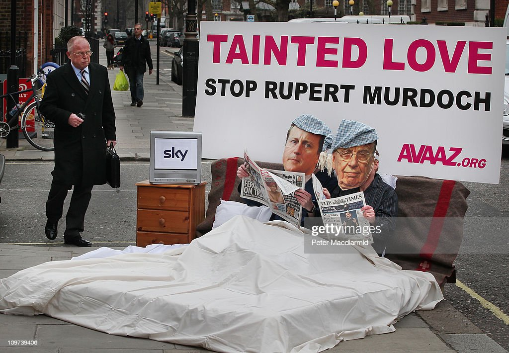 A passerby looks on as two activists dressed as Prime Minister <a gi-track='captionPersonalityLinkClicked' href=/galleries/search?phrase=David+Cameron+-+Pol%C3%ADtico&family=editorial&specificpeople=227076 ng-click='$event.stopPropagation()'>David Cameron</a> (L in bed) and News Corporation owner Rupert Murdoch share a bed in a stunt outside a media and broadcasting conference on March 3, 2011 in London, England. The British government has given the go-ahead for Rupert Murdoch's News Corporation to takeover satellite broadcaster BSkyB. The deal has been allowed after News Corporation offered to spin off Sky News.