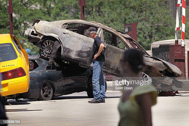 A passerby looks on as workers stage a car accident on the Michigan Avenue bridge during the filming of the movie Transformers 3 July 16 2010 in...