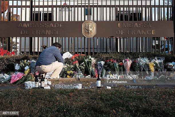 A passerby pays respects at a makeshift memorial at the entrance of the French Embassy on November 14 2015 in Washington DC A series of coordinated...