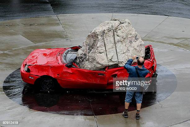 A passerby photographs an unusual sculpture showing a large boulder smashed on top of a car on a roundabout near Walsh Bay on Sydney Harbour on...
