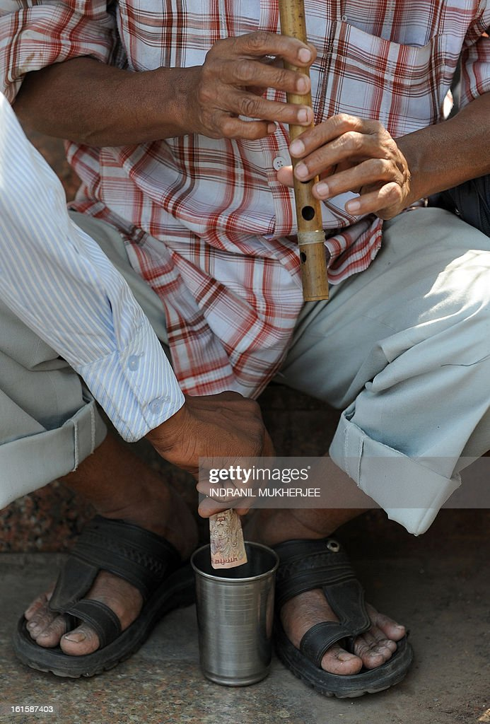 A passerby places a ten rupee note for visually impaired Mohammad Ismail, 58, who busks on the steps of a railway station in Mumbai on February 12, 2013. Ismail, who lost his eyesight to an ailment during his early childhood, continued to do odd jobs until he learned playing the flute several years ago. He collects an average of 100 rupees (USD 2) per day as alms by playing the instrument. AFP PHOTO/Indranil MUKHERJEE