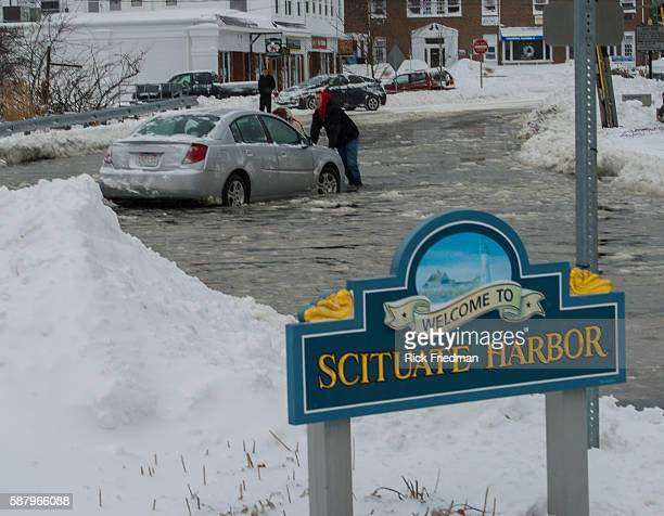 A passerby pushes a car out of a flooded area during the a Nor'easter winter storm in Scituate MA on January 3 2014 The winter dumped up to 2 feet of...