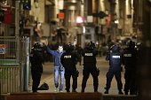 A passerby raises his arms in front of Police forces in the northern Paris suburb of SaintDenis city center on November 18 as Police special forces...