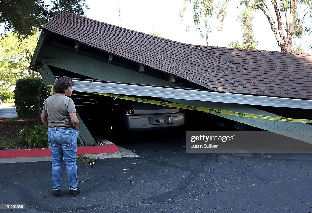A passerby stops to look at a collapsed carport following a 6.0 earthquake on August 24, 2014 in Napa, California. A 6.0 earthquake rocked the San Francisco Bay Area shortly after 3:00 am on Sunday morning causing damage to buildings and sending at least 70 people to a hospital with non-life threatening injuries.