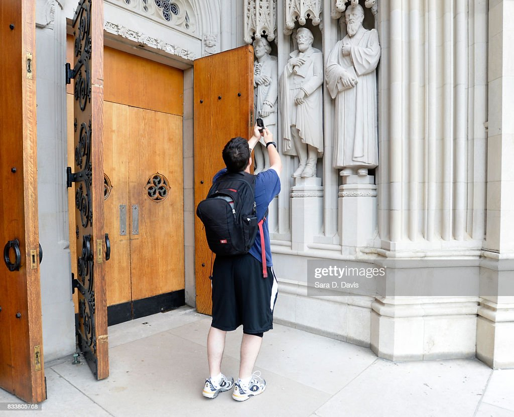 A passerby stops to take a mobile phone photo of a statue on the portal of Duke University Chapel, seen here in middle right, bearing the likeness of Confederate General Robert E. Lee was vandalized on early August 17, 2017 in Durham, North Carolina. The statue is one of 10 historical figures adorning the exterior of the chapel; the group includes significant figures from the American South and the Protestant and Methodist traditions.